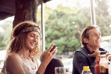 Young Woman Text Messaging On Smart Phone While Sitting With Man In Cafe