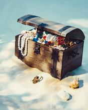 Treasure Chest Filled With Jewels And Gold Coins On Sandy Beach