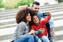 Happy Family Taking Selfies In A Park
