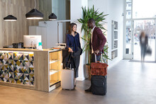 Business People Waiting With Luggage At Hotel Reception