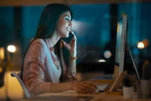 Relaxed Young Woman On The Phone Working At Desk In Office