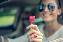 Happy Young Woman Showing Heart Shape Lollipop During Road Trip