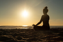 Woman Meditating On The Beach Against Evening Sun