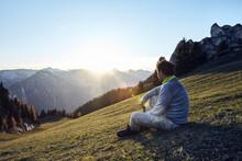 Austria, Tyrol, Rofan Mountains, Hiker Sitting On Meadow At Sunset