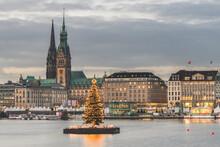 Germany, Hamburg, Illuminated Alstertanne Tree At Dusk With Jungfernstieg Promenade And Saint Nicholas Church In Background