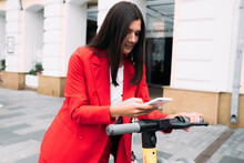 Beautiful Businesswoman Scanning QR Code On Electric Push Scooter