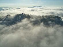 Aerial View Of Low Clouds Shrouding Forested Hills