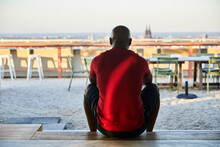 Mature Man In Red T-shirt Sitting On Steps At Rooftop During Sunset