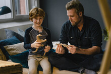 Portrait Boy Sitting With His Father On Couch Kneading Dinosaur
