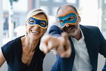 Businessman And Woman Wearing Super Hero Masks, Pointing At Camera
