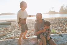 Smiling Father With Children Sitting On Driftwood At Beach