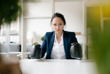 Portrait Of Young Businesswoman Sitting At Desk Wearing Boxing Gloves