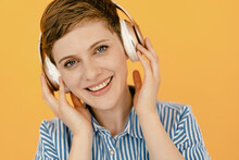 Portrait Of Happy Woman Listening To Music With Orange Background