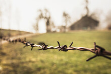 Old Barbed Wire Fence With Farmhouse In Background