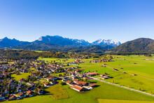 Germany, Bavaria, Upper Bavaria, Werdenfelser Land, Krun, Aerial View Of Green Fields And Village With Wetterstein Mountains In Background