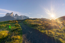 Chile, Ultima Esperanza Province, Empty Dirt Road In Torres Del Paine National Park At Sunset With Cuernos Del Paine In Background