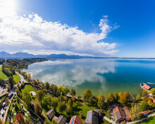 Germany, Bavaria, Chieming, Clouds Over Chiemsee Lake And Lakeshore Houses On Sunny Autumn Day