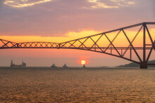 United Kingdom, Scotland, Firth Of Forth, Forth Rail Bridge With Tug Boats Underneath And Hound Point Oil Loading Marine Terminal At Sunset