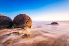 Moeraki Boulders In Sea Against Sky At Koekohe Beach, South Island, New Zealand