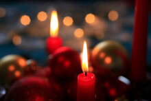 Red Burning Advent Candles And Christmas Baubles