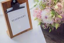 Germany, Bridal Bouquet Lying Beside Clipboard With Reservation Sign