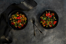Two Bowls Of Stir-fried Vegan Salad With Eggplants, Paprika And Parsley