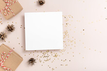 Christmas. Blank Square Paper Mockup, Golden Stars Confetti, Bumps, Gift Boxes On Beige Background
