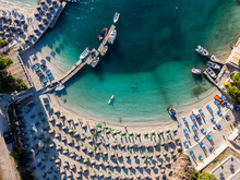 Aerial Drone View Of Exotic Sandy Beach At Summer. Parasols And Deck Chairs On Beach, View From Above. Colorful Sea Water.