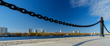 A Fragment Of A Cast-iron Chain Fence On The River Embankment. In The Background, Water, Blue Skies And High-rise Buildings On The Opposite Bank Of The River. Sunny Day. Panorama.