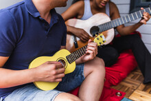 Anonymous Diverse Couple Playing Ukulele And Guitar