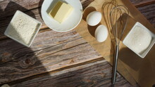 White Chicken Eggs Metal Whisk For Whipping Bowls With Sugar And Flour Slices Of Butter On A Saucer On A Wooden Surface Sun Rays Breakfast Baking Ingredients