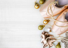 Christmas Flat Lay Pair Of Pink Pointe Shoes, Christmas Tree, Golden Balls, Gold Star, Pearl Beads On White Wooden Background. Christmas Concept, Top View, Copy Space, Monochrome