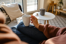 A Cup Of Tea Or Coffee In The Hands Of A Girl. In The Morning, The Girl Drinks Hot Tea. Enjoy The Comforts Of Home. White Cup Close-up In The Hands Of A Woman In The Rays Of The Sun From The Window
