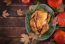 Roasted Turkey Garnished With Cranberries On A Rustic Style Table Decorated With Pumpkins, Apples And Autumn Leaf. Thanksgiving Day. Flat Lay. Top View