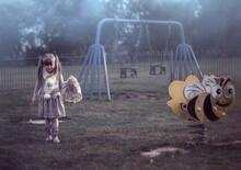 Creepy, Foggy Playground With A Little Girl Holding A Teddy Bear