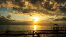 The Rising Sun Shines Through The Clouds, Sunny Path On The Water, Calm Sea And An Empty Beach