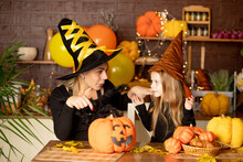 Halloween, Mom And Daughter Child In A Witch Costume With Pumpkins And A Big Spider In A Dark Kitchen Scare Each Other During The Halloween Celebration