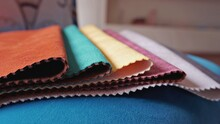 Close-up Folded Colored Upholstery Fabric Samples On Blue Background. Example For Fabric Catalog. Selective Focus.
