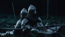 Two Medieval Knights Sitting On Battlefield Amidst Dead Enemies. Last Surviving Crusaders, Soldiers, Warriors After Battle. Destruction Of War, Invasion, Crusade. Cinematic Historic Reenactment
