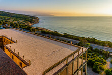 Roof Of An Abandoned Structure In The Sunset With Beach And Ocean