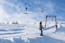 Man Snowboarder Using Ski Yoke To Get On The Top Of The Mountains
