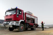 Firefighter Standing Near Fire Engine