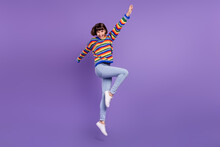 Photo Of Crazy Careless Pretty Lady Jump Raise Hand Wear Striped Pullover Jeans Footwear Isolated Purple Color Background