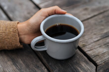 Crop Hand With Coffee On Wooden Table