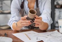 Crop Potter Examining Crockery Over Sketches