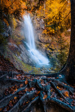 Mystic Waterfall In A Fall Landscape And Golden Trees.
