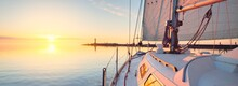 White Yacht Sailing After The Rain At Sunset. Close-up View From The Deck To The Bow. Clear Blue Sky With Glowing Clouds Reflecting In A Still Water. Idyllic Seascape. Sea, Cruise, Travel Destinations