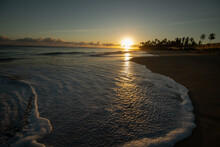 Sunset On Sandy Beach Waves Coming To Shore Golden Glow And Reflection Of Sun On Sand White Foamy Waves Coming Into Shore And Receding Leaving Wet Sand Reflecting Sunrise