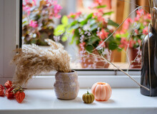 Preparations For Halloween, Pumpkin-shaped Candles And A Vase With A Dry Bouquet On The Windowsill, The Atmosphere Of Anticipation Of Halloween And Memorial Day, A Cozy Composition Of Candles