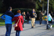 Para młodych ludzie, kobieta i mężczyzna spaceruje deptakiem, chodnikiem w parku.